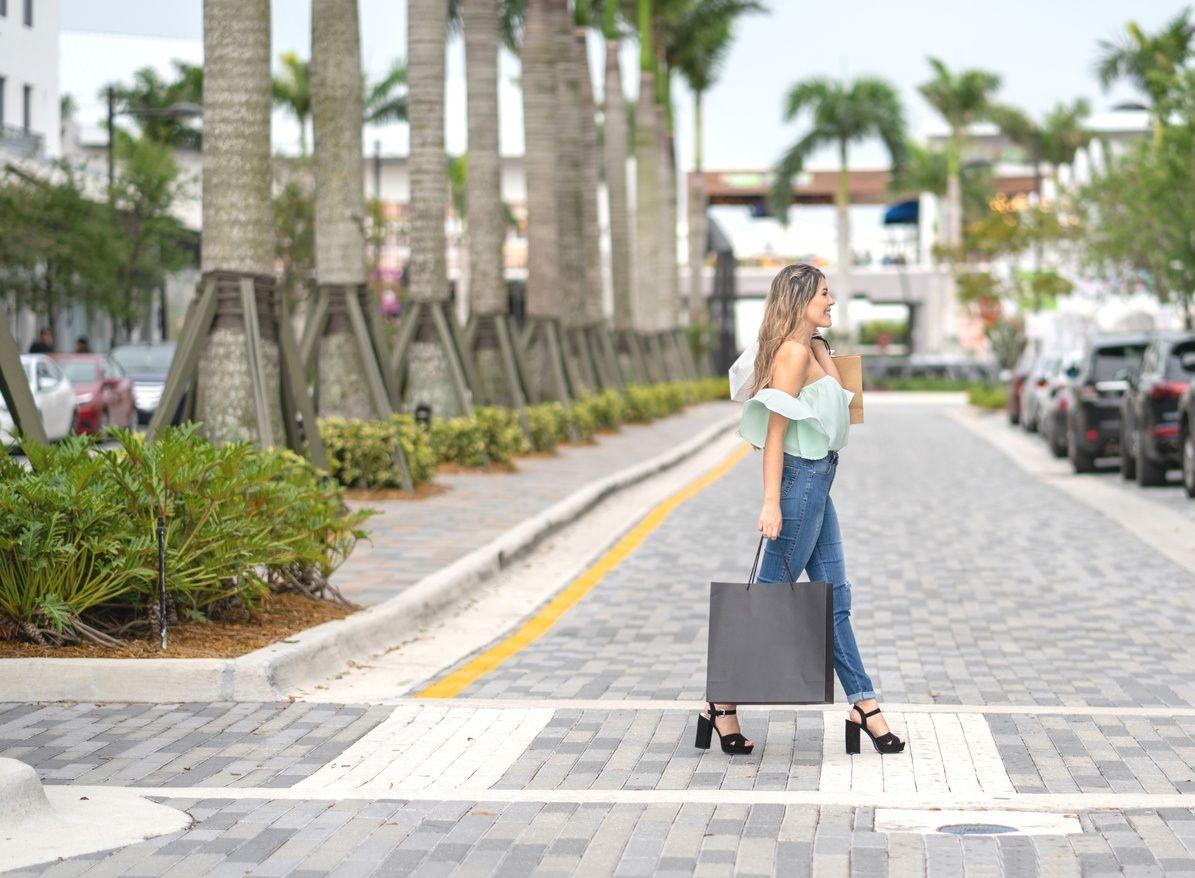 bir alışveriş çantası tutan ve Coral Gables caddeyi geçen kadın